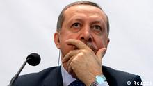 Turkey's Prime Minister Tayyip Erdogan listens during a news conference after the opening session of the fifth United Nations Alliance of Civilizations (UNAOC) Forum in Vienna February 27, 2013. REUTERS/Heinz-Peter Bader (AUSTRIA - Tags: POLITICS)