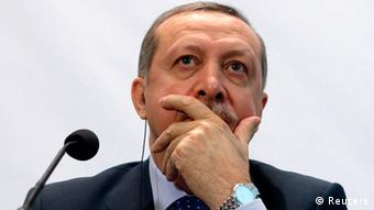Turkish Prime Minister Recep Tayyip Erdogan holds his hand pensively over his mouth while sitting at a podium. (Photo: Heinz-Peter Bader/REUTERS)