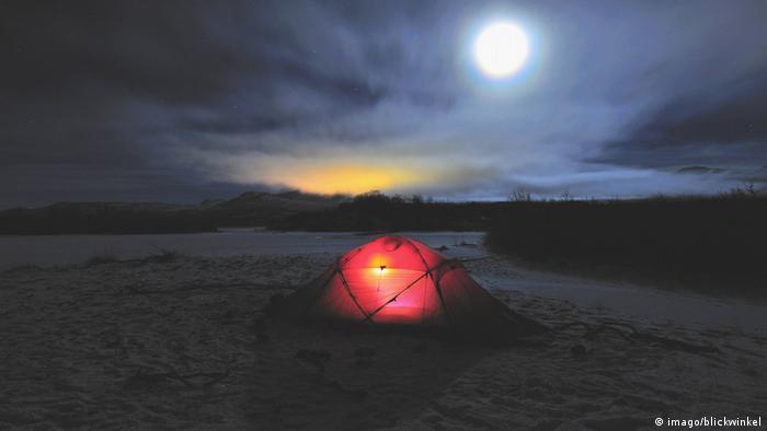Ein beleuchtetes, einsames Zelt in nächtlicher Landschaft