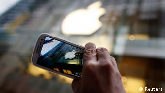 A passerby photographs an Apple store logo with his Samsung Galaxy phone in central Sydney in this September 21, 2012, file photo. Apple Inc lost a major ruling in its ongoing patent battle with Samsung Electronics on March 1, 2013, as a federal judge threw out part of a jury's $1.05 billion damages award against Samsung over a variety of phone products. REUTERS/Tim Wimborne/Files (AUSTRALIA - Tags: BUSINESS TELECOMS SCIENCE TECHNOLOGY)