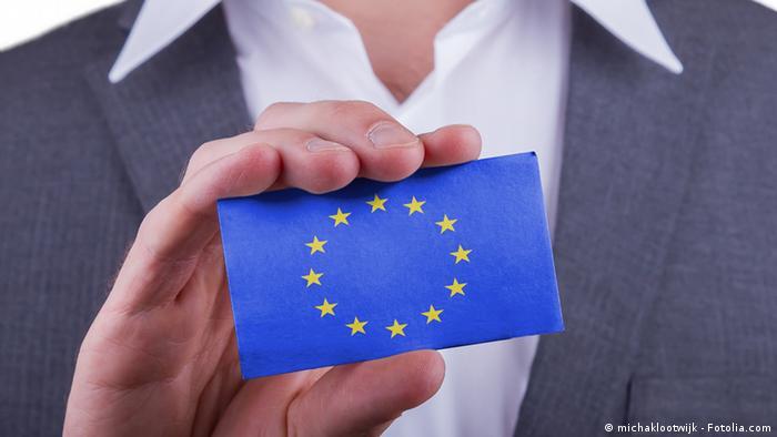 Мужчина в костюме держит карточку с символом ЕС