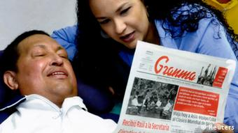REFILE - QUALITY REPEAT Venezuela's President Hugo Chavez holds a copy of the newspapers as his daughters, Rosa Virginia (R) and Maria watch while recovering from cancer surgery in Havana in this photograph released by the Ministry of Information on February 15, 2013. Venezuela's government published the first pictures of cancer-stricken Chavez since his operation in Cuba more than two months ago, showing him smiling while lying in bed reading a newspaper, flanked by his two daughters. The 58-year-old socialist leader had not been seen in public since the Dec. 11 surgery, his fourth operation in less than 18 months. The government said the photos were taken in Havana on February 14, 2013. REUTERS/Ministry of Information/Handout (VENEZUELA - Tags: POLITICS PROFILE HEALTH) ATTENTION EDITORS - THIS IMAGE WAS PROVIDED BY A THIRD PARTY. FOR EDITORIAL USE ONLY. NOT FOR SALE FOR MARKETING OR ADVERTISING CAMPAIGNS. THIS PICTURE IS DISTRIBUTED EXACTLY AS RECEIVED BY REUTERS, AS A SERVICE TO CLIENTS