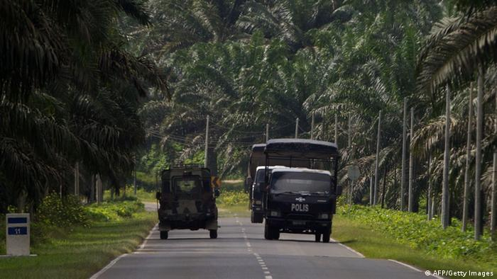 Malaysian police (R) and an army truck drive past each other in Lahad Datu on the Malaysian island of Borneo on March 3, 2013, near the area where the stand-off with Sulu gunmen took place in Tanduo village on March 1. A Malaysian policeman was killed by 'militants' in a region where Filipino followers of a self-claimed sultan are holed up in a deadly standoff with security forces, state media reported on March 3, 2013. (Photo: MOHD RASFAN/AFP/Getty Images)