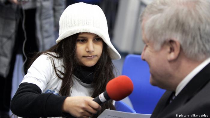 Eine zehnjährige Mitarbeiterin von Radijojo (links) interviewt den Politiker Horst Seehofer (rechts). Sie hält ein Mikrofon in der Hand