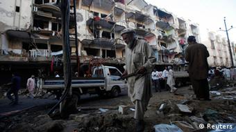 Men work near the damaged building after a bomb blast in a residential area, a day earlier, in Karachi March 4, 2013. (Photo: Reuters/Athar Hussain)