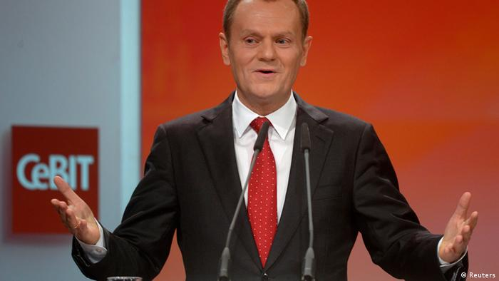 A man wearing a black business suit, white dress shirt and red tie gestures emphatically with both arms as he speaks into a microphone before a white and red background. Photo: Fabian Bimmer