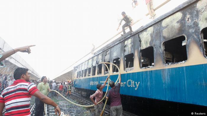 People help to control a fire of a burnt compartment of a train at Kamlapur Railway Station in Dhaka March 4, 2013. Three compartments of a train, which runs between Dhaka and Noakhali, stationed at Kamalapur was set on fire on the second day of Bangladesh Jamaat-e-Islam�s country wide two-day strike. Bangladesh Railways Minister Mazibul Hoque accused Bangladesh Jamaat-Shibir activists for the attack, after visiting the site, local media reported. REUTERS/Andrew Biraj (BANGLADESH - Tags: DISASTER TRANSPORT CRIME LAW CIVIL UNREST)