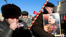 A man holds a board displaying an illustration of the late Soviet leader Josef Stalin before a wreath-laying ceremony to mark the 60th anniversary of his death in Red Square in central Moscow March 5, 2013. REUTERS/Sergei Karpukhin (RUSSIA - Tags: ANNIVERSARY POLITICS SOCIETY)