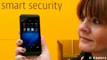 A woman poses with a BlackBerry Z10 smartphone featuring high security Secusite software, used for governmental communication, at the booth of Secusmart during preparations at the CeBit computer fair in Hanover, March, 4, 2013. The biggest fair of its kind open its doors to the public on March 5 and will run till March 9, 2013. REUTERS/Fabrizio Bensch (GERMANY - Tags: BUSINESS SCIENCE TECHNOLOGY)