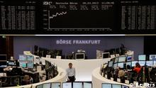 Traders are pictured at their desks in front of the DAX board at the Frankfurt stock exchange March 5, 2013. REUTERS/Remote/Janine Eggert (GERMANY - Tags: BUSINESS)