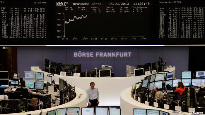 Traders are pictured at their desks in front of the DAX board at the Frankfurt stock exchange March 5, 2013. (Janine Eggert/REUTERS)
