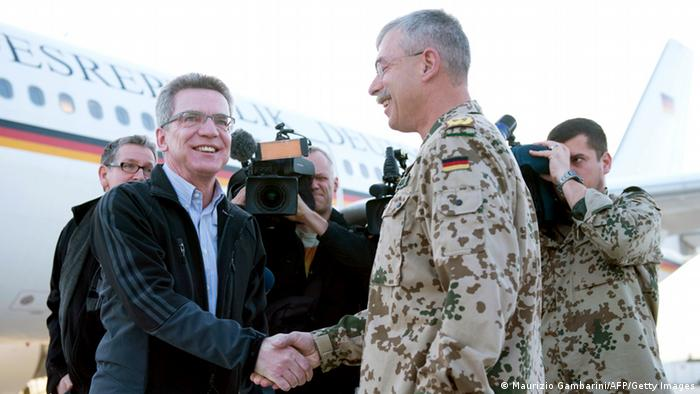 German Defence Minister Thomas de Maiziere (L) shakes hands with German Bundeswehr commandant RC North, Major General Joerg Vollmer upon his arrival at the airport of Mazar-i-Sharif, Afghanistan on March 05, 2013. De Maiziere announced on March 05, 2013 that the German army Bundeswehr will clear the base in Kunduz, northern Afghanistan in the upcoming weeks. AFP PHOTO / POOL/MAURIZIO GAMBARINI (Photo credit should read MAURIZIO GAMBARINI/AFP/Getty Images)
