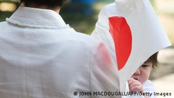 A Japanese baby girl plays with a Japanese flag as her mother waits for Japan's Crown Prince Naruhito to arrive prior to his visit to the Japanese International school and the Conradschule in Berlin June 24, 2011 (Photo: JOHN MACDOUGALL/AFP/Getty Images)