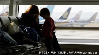 A mother and her child waitat the airport (Photo: TOSHIFUMI KITAMURA/AFP/Getty Images)