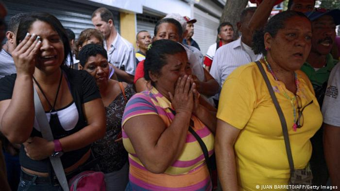 Supporters of Venezuelan President Hugo Chavez cry after knowing of his death in Caracas on March 5, 2013. AFP PHOTO / JUAN BARRETO (Photo credit should read JUAN BARRETO/AFP/Getty Images)