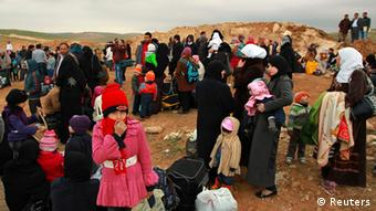 Syrian refugees take a rest after they crossed into Jordanian territory with their families from Syria into Jordan near Mafraq February 18, 2013. According to the Jordanian Armed Forces sources, around 89,000 Syrian refugees fleeing from the violence in their country have crossed the Jordanian border since the beginning of 2013.