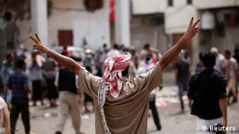 A man wearing a red-and-white turban raises his hands to show support during a protest march.