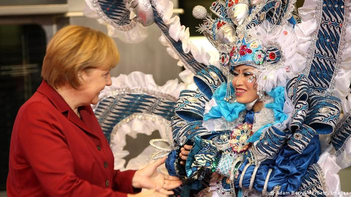 German Chancellor Angela Merkel (L) is greeted by an Indonesian hostess at the ITB Berlin tourism convention (Internationale Tourismus-Boerse) prior to its opening in Berlin on March 5, 2013. The ITB Berlin runs from March 6-10 and features Indonesia as its partner country for the event in 2013. AFP PHOTO / ADAM BERRY (Photo credit should read ADAM BERRY/AFP/Getty Images)