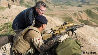 German Defence Minister Thomas de Maiziere speaks to a soldier as he visits OP North near Masar-i-Scharif, March 5, 2013. REUTERS/Maurizio Gambarini/Pool