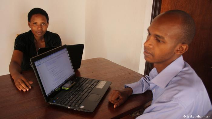 Software developers in Rwanda, sitting at a table with a laptop