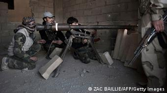 Rebels fighters prepare to fire a portable canon against an adjacent Syrian government-held building during fighting on February 27, 2013 in the Hawiqah neighbourhood of the eastern Syrian town of Deir Ezzor. Syria's opposition and foreign powers hold crucial talks in Rome with Washington suggesting it is ready to boost support to rebels in their struggle against President Bashar al-Assad. AFP PHOTO/ZAC BAILLIE (Photo credit should read ZAC BAILLIE/AFP/Getty Images)