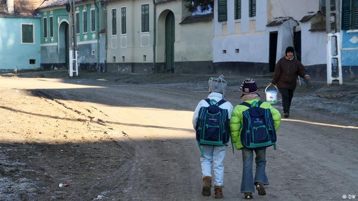 Copii care merg la școală într-un sat din România