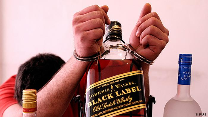A person is handcuffed to a bottle of Johnny Walker in Iran (Photo: Copyright: FARS)