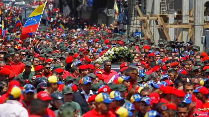 A Venezuelan national flag (L) is seen as the coffin of deceased Venezuelan leader Hugo Chavez is driven through the streets of Caracas (Photo: REUTERS/Carlos Garcia Rawlins)