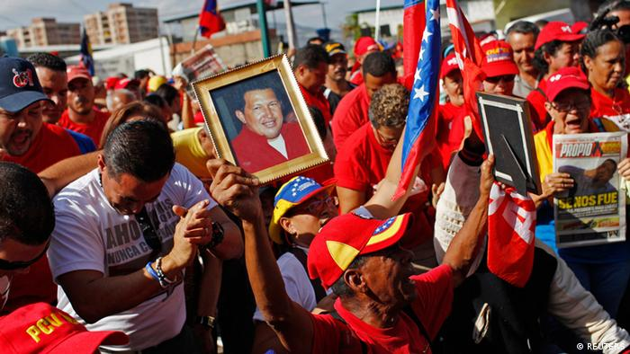Supporters of deceased Venezuelan leader Hugo Chavez carry pictures of Chavez as they react while his coffin is driven through the streets of Caracas, March 6, 2013. Venezuela's late President Chavez died on Tuesday of cancer, and authorities have not yet said where he will be buried after his state funeral on Friday. REUTERS/Carlos Garcia Rawlins (VENEZUELA - Tags: POLITICS OBITUARY)