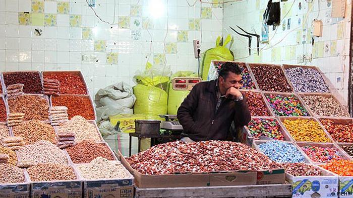 Продавец на рынке среди лотков
