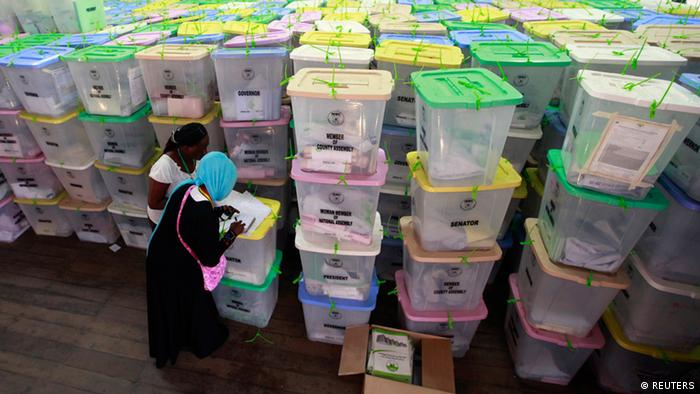 Polling clerks recording information on a pile of ballot boxes in Kenya