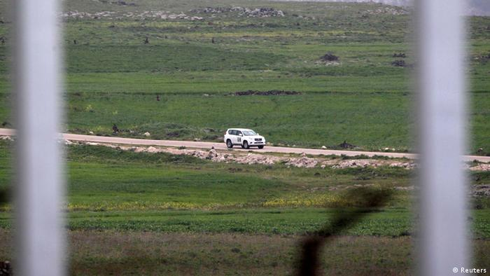 A United Nations vehicle drives near the Syrian village of Al Jamla, close to the ceasefire line between Israel and Syria, as seen from the Israeli occupied Golan Heights March 5, 2013. Syrian rebels have seized a convoy of U.N. peacekeepers near the Golan Heights and say they will hold them captive until President Bashar al-Assad's forces pull back from a rebel-held village which has seen heavy recent fighting. Picture taken March 5, 2013. REUTERS/Baz Ratner (POLITICS CIVIL UNREST)