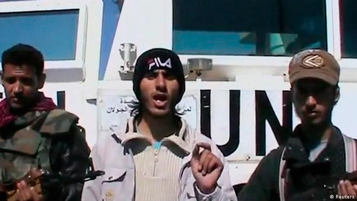 A member of the Al Yarmouk Martyr brigade makes a statement in front of a white vehicle with 'UN' written on it at what said to be Jamla, Syria near Golan Heights on March 6, 2013 in this still image taken from video posted on social media website.