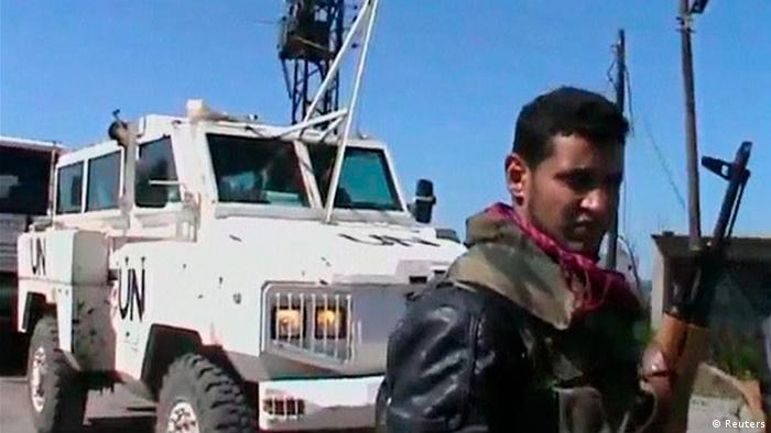 An armed member of the Al Yarmouk Martyr brigade is seen in front of a white vehicle with 'UN' written on it at what said to be Jamla, Syria near Golan Heights on March 6, 2013 in this still image taken from video posted on social media website. Syrian rebels have seized a convoy of U.N. peacekeepers near the Golan Heights and say they will hold them captive until President Bashar al-Assad's forces pull back from a rebel-held village which has seen heavy recent fighting. The capture was announced in rebel videos posted on the Internet and confirmed on Wednesday by the United Nations in New York, which said about 20 peacekeepers had been detained. REUTERS/Social Media Website via Reuters TV (SYRIA - Tags: CIVIL UNREST POLITICS) ATTENTION EDITORS - THIS PICTURE WAS PROVIDED BY A THIRD PARTY. REUTERS IS UNABLE TO INDEPENDENTLY VERIFY THE AUTHENTICITY, CONTENT, LOCATION OR DATE OF THIS IMAGE. FOR EDITORIAL USE ONLY. NOT FOR SALE FOR MARKETING OR ADVERTISING CAMPAIGNS. NO SALES. NO ARCHIVES. THIS PICTURE IS DISTRIBUTED EXACTLY AS RECEIVED BY REUTERS, AS A SERVICE TO CLIENTS