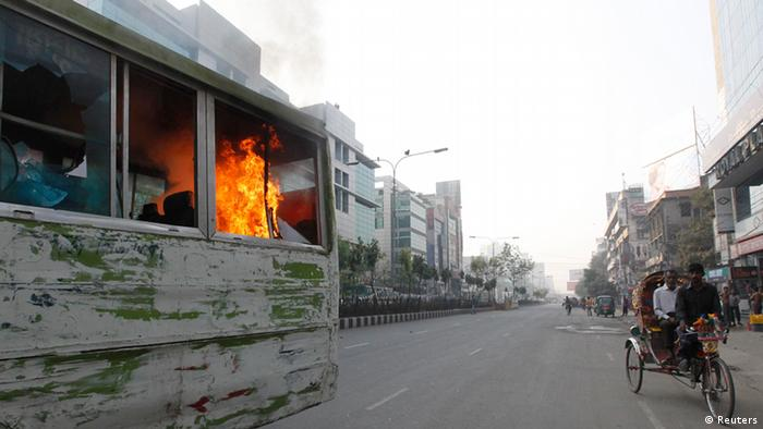 A rickshaw passes a burnt bus after activists of Bangladesh Nationalist Party (BNP) vandalized and set fire to it during a country wide strike in Dhaka March 7, 2013. Bangladesh Nationalist Party and it's alliance called the daylong strike in protest against what it said were violence and killings by the police in their protest rally over war tribunals on Wednesday, local media reported. REUTERS/Andrew Biraj (BANGLADESH - Tags: POLITICS CIVIL UNREST TPX IMAGES OF THE DAY)