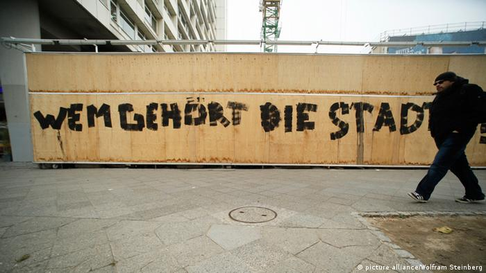 Graffiti in Berlin reading: Who does the city belong to?