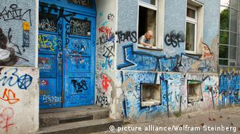 An elderly woman looks out of the window of a graffiti covered Berlin apartment. Photo: Wolfram Steinberg.