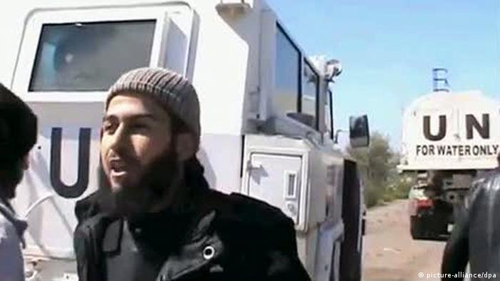 A bearded Arabic man wearing a religious hat looks off camera in a desert setting with a white truck behind that reads UN.