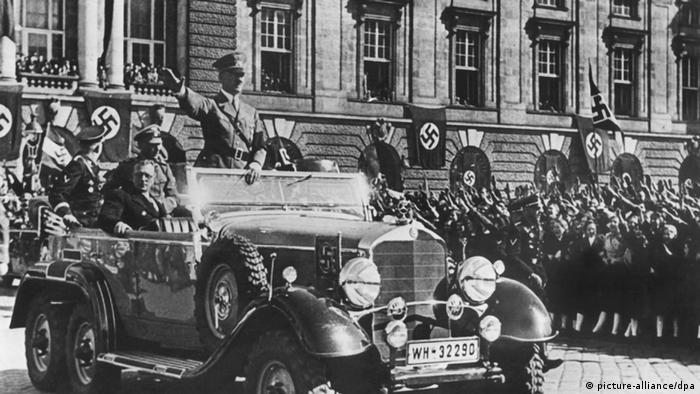 Hitler does the Nazi salute from a car while Nazi flags hang in the background in Vienna