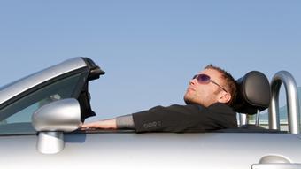 Ein junger Mann relaxt im Cabrio vor klarem Himmel