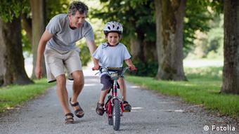 Ein Vater bringt seinem Kind das Radfahren bei.