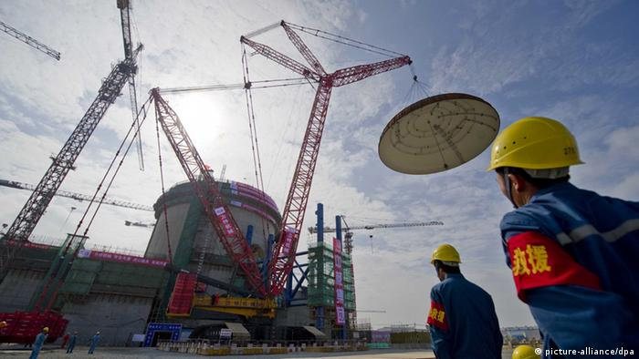 Workers watch the dome of the containment structure for the No.1 reactor being hoisted at the contruction site of the Changjiang Nuclear Power Plant in Tangxing village, Haiwei Township,