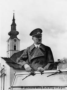 Hitler im offenen Wagen stehend bei seinem Einzug in Braunau am Inn (Foto: picture-alliance)