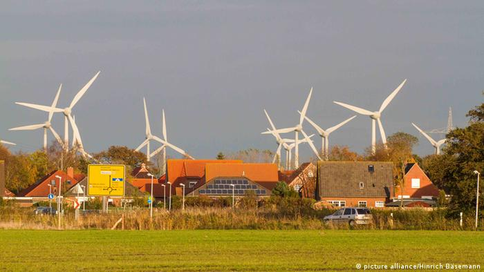 Windmills and solar panels are seen in a village in East Friesland. (Photo: picture alliance/ Hinrich Bäsemann)