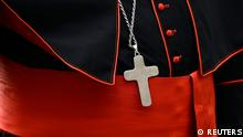 A cross rests on a cardinal's cassock as he arrives for a meeting in the Synod Hall at the Vatican March 8, 2013. REUTERS/Dylan Martinez (VATICAN - Tags: RELIGION)