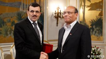 Tunisian President Moncef Marzouki (R) shakes hands with Prime Minister Ali Larayedh in Tunis March 8, 2013. Larayedh unveiled a new Islamist-led coalition government on Friday that he said would serve only until an election is held before the end of the year. REUTERS/Zoubeir Souissi (TUNISIA - Tags: POLITICS)