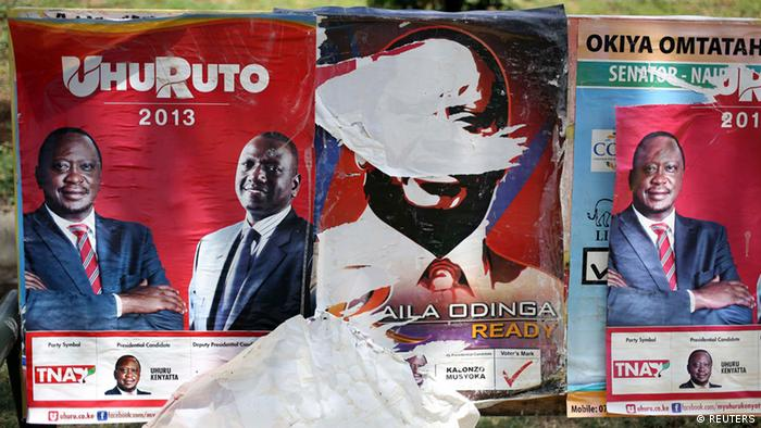 Posters of presidential candidates Uhuru Kenyatta and Prime Minister Raila Odinga (C) are seen in Nairobi March 8, 2013. Kenya's presidential race tightened on Friday with frontrunner Kenyatta gaining just under half of the ballots counted four days after the vote, raising the prospect of a tense run-off against his main rival Odinga. REUTERS/Goran Tomasevic (KENYA - Tags: POLITICS ELECTIONS)