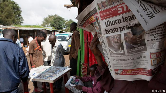 Kenyans read newspapers reporting on the 2017 general election