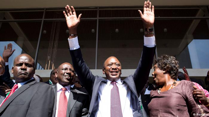 Uhuru Kenyatta as presidential candidate greets supporters beside running mate William Ruto