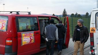Flüchtlinge zwischen ihren zwei Kleinbussen (Foto: DW/Stephanie Höppner)
